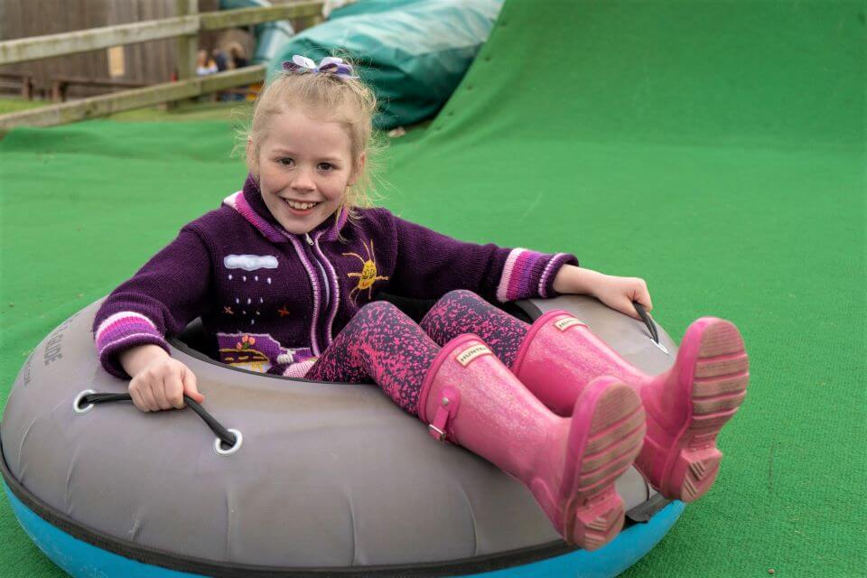 Child with pink wellies on an inflatable tyre at Adventure Valley.