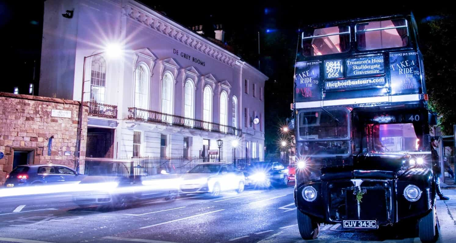 A ghost bus tour bus stopped on the street at night time.