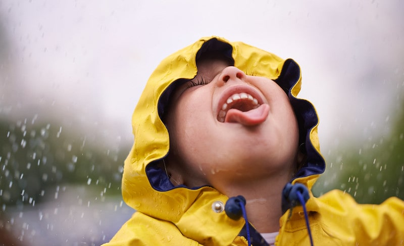 Little child wearing a yellow raincoat, hood up, standing in the rain and sticking out their tongue to catch the falling raindrops.