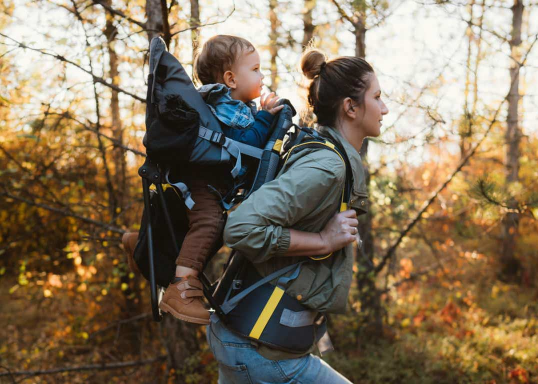 Mother carrying a baby in a baby carrier backpacks