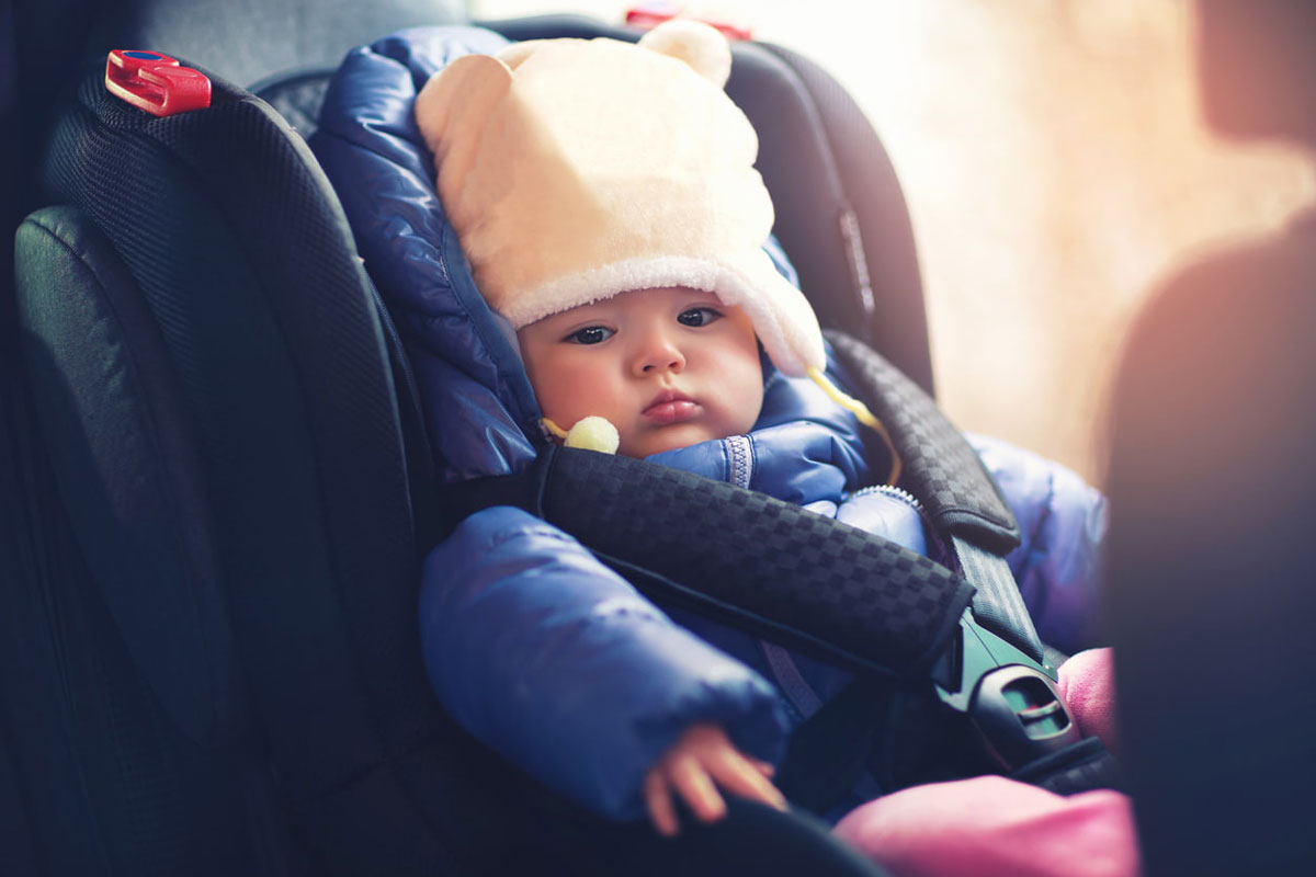 Baby girl sitting in swivel car seat