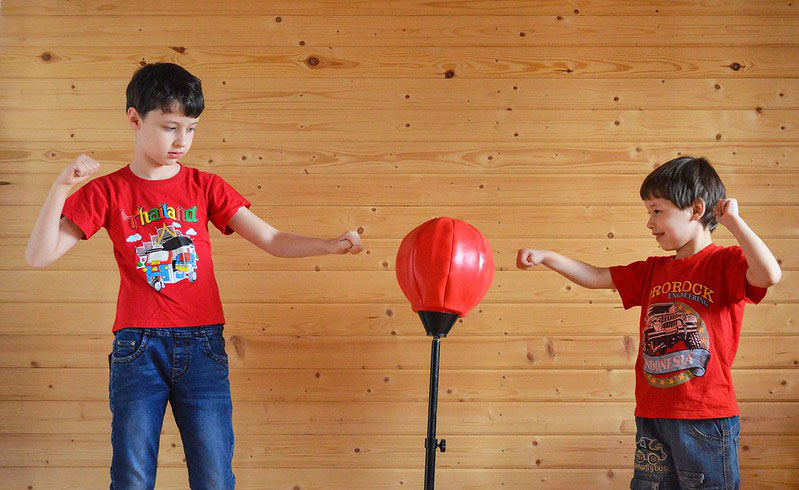 Kids hitting punching ball together inside
