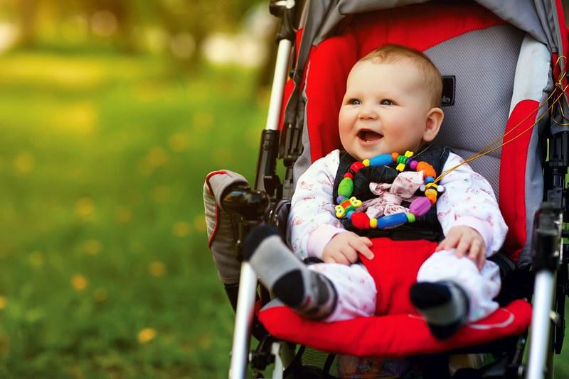 Baby enjoys sitting in a stroller.