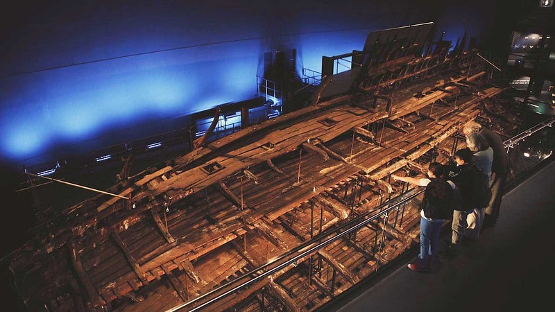 People looking at the shipwreck remains in The Mary Rose museum.