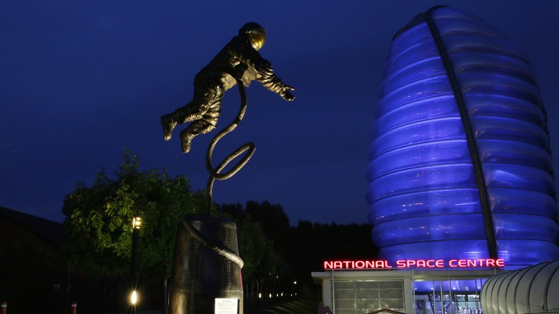 A model space man and the famous Rocket Tower at the National Space Centre at night.