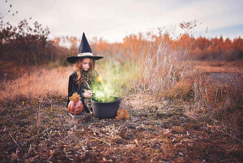 Young girl making a witch potion in a cauldron