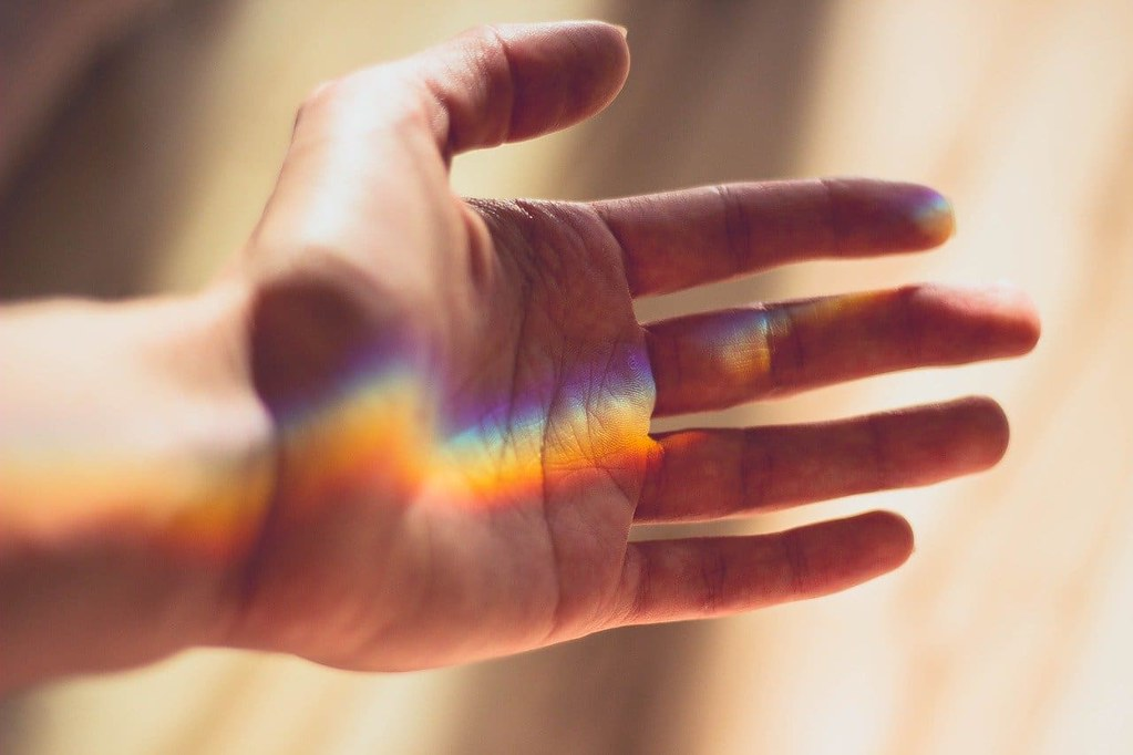 A hand held out with a rainbow of refracted light on it.