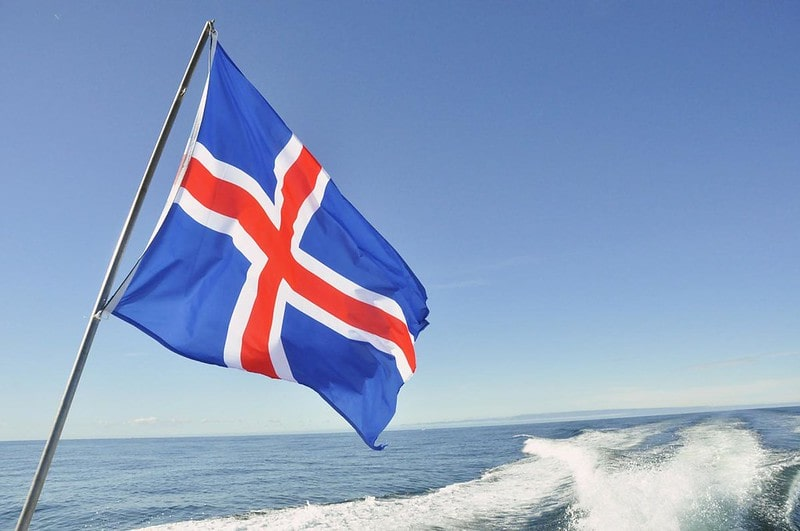 A blue, red and white Icelandic flag flying on the back of a boat.