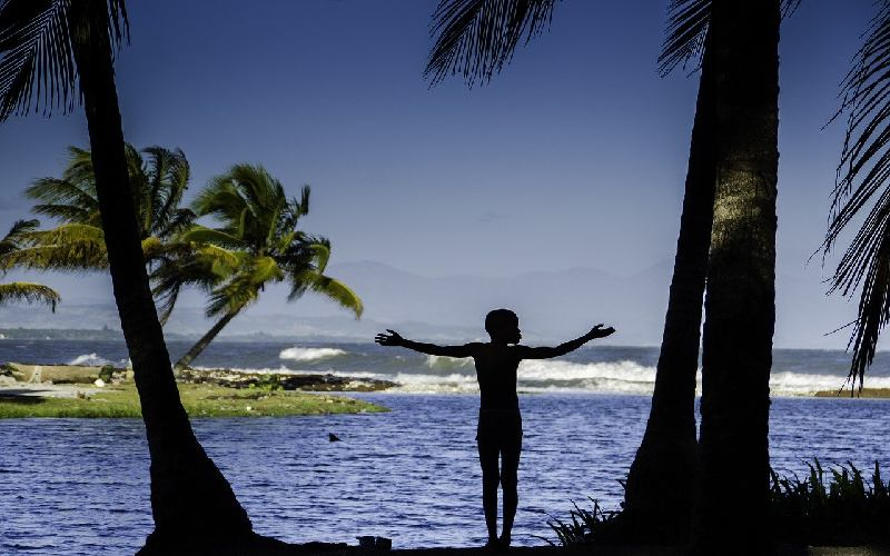 Silhouette of a young boy by the sea in Haiti.