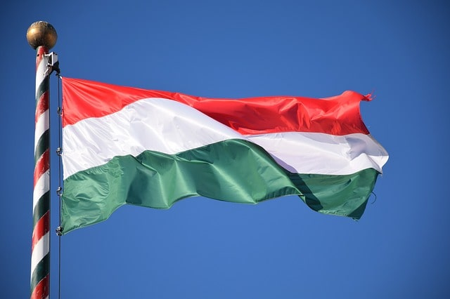 The red, white and green Hungarian flag flies against a backdrop of blue sky.