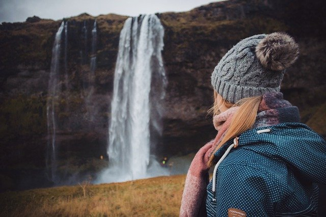 An Icelandic girl with her back to the camera looks at a waterfall in Iceland.
