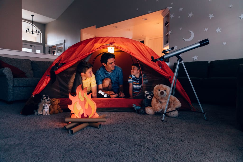 Family camping in a tent inside making a fun outdoor activity an indoor activity for the kids.
