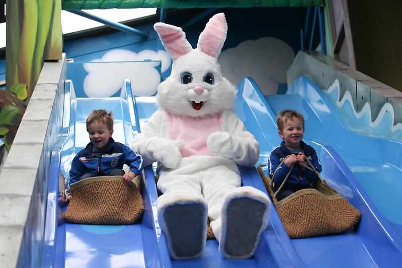 Kids riding down blue slide with BIG Sheep mascot.