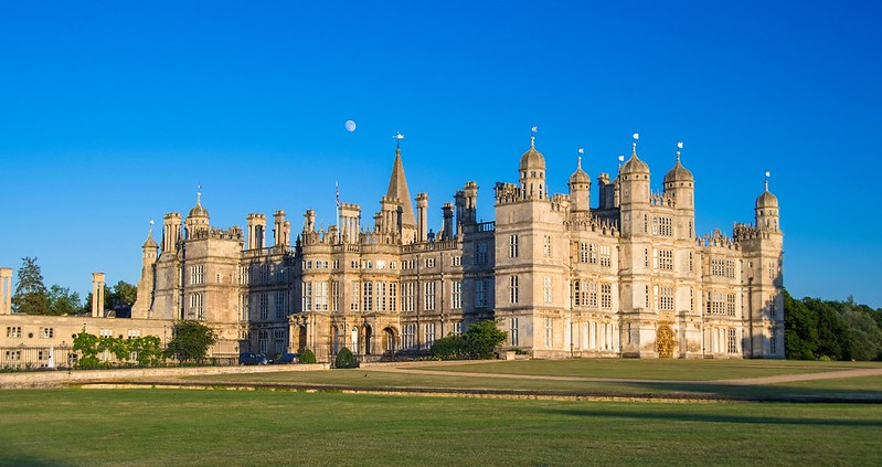 Burghley House and greenery in front of building exterior.