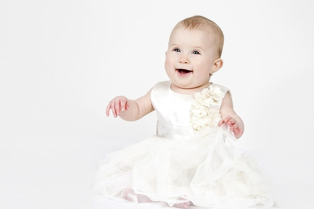 A happy smiling baby wearing a gorgeous white dress.