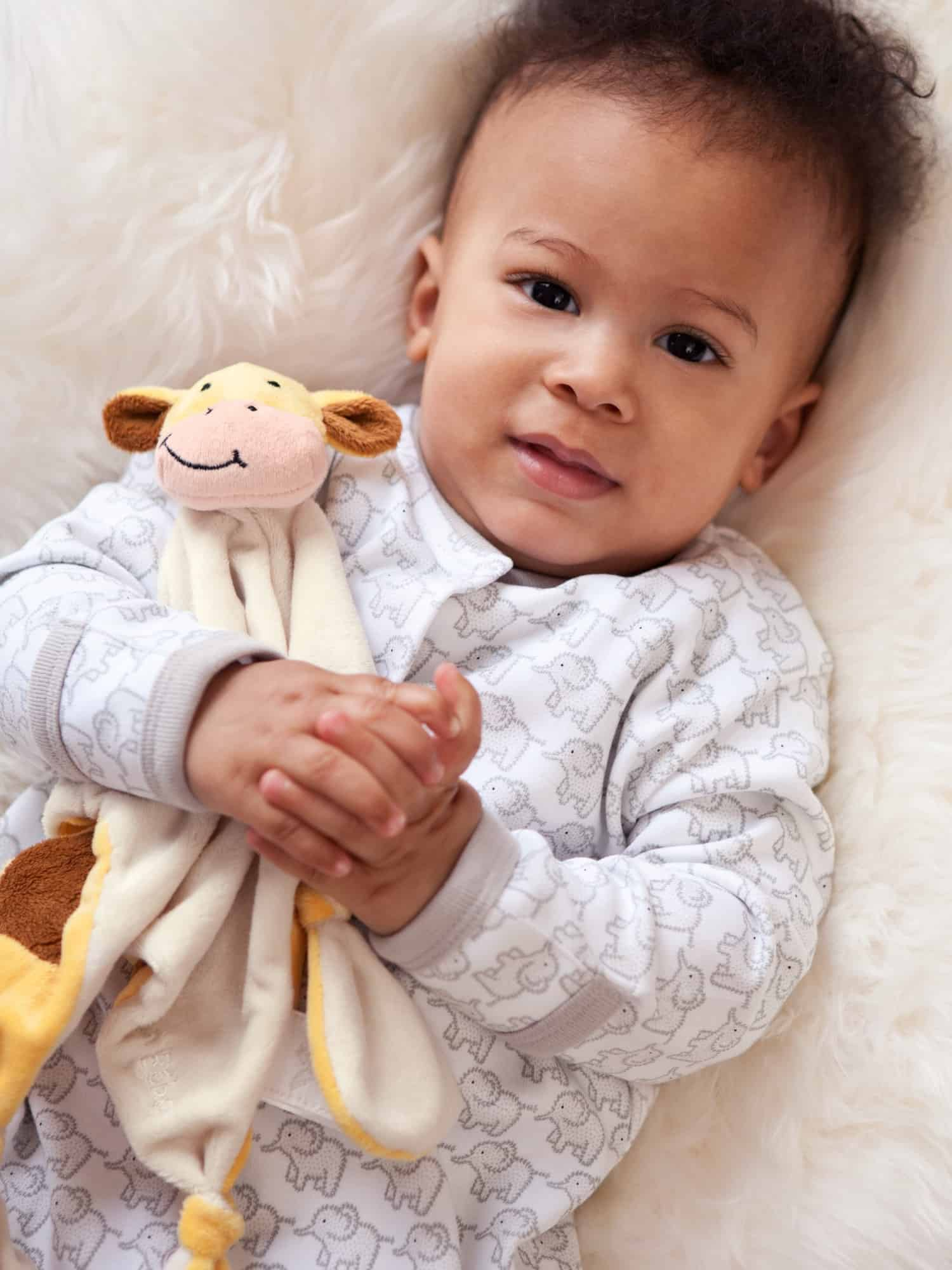 Baby holding extra soft and cuddly giraffe comforter.