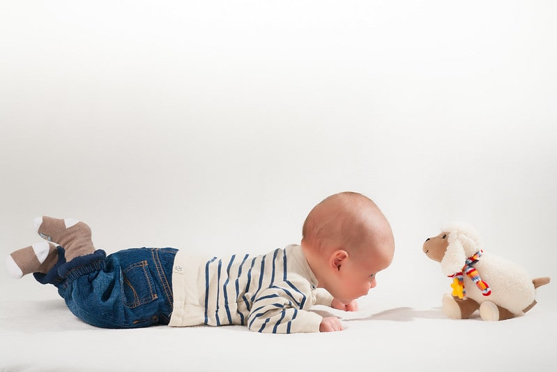 Charming little boy happily playing with his plush toy.