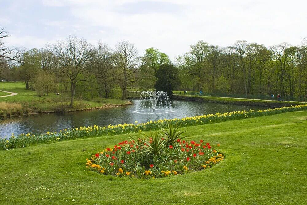 View of Astley Hall fountain with a lush green garden around it.