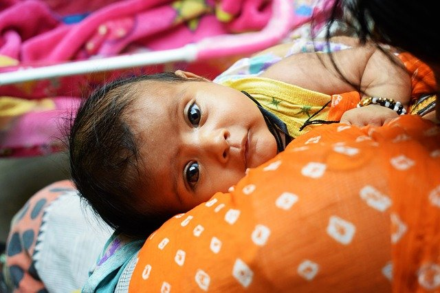 A baby girl looks at the camera whilst lying in her mother's arms.