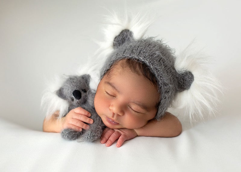 A newborn baby sleeps peacefully wearing a grey bonnet against a white backdrop.