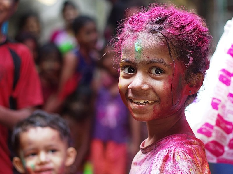 A young girl covered in bright coloured paint turns and smiles at the camera whilst celebrating a traditional Indian festival.