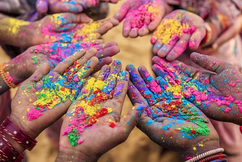 Alt text: A close up image of a group of children's hands at the Indian Holi festival.