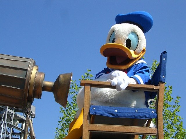 Disney's Donald Duck sitting in a director's chair.
