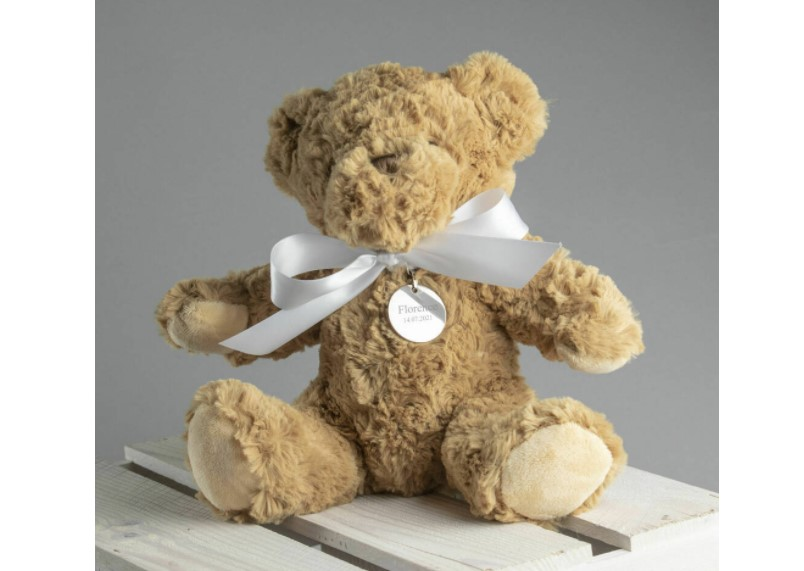 A cuddly personalized Teddy Bear tied with soft white ribbon.