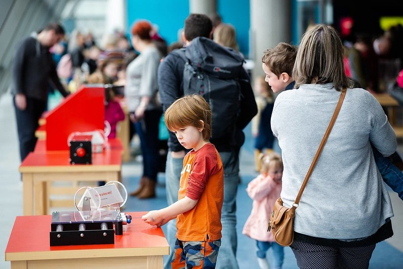 A young child engrossed in a science display at the Glasgow Science Centre.