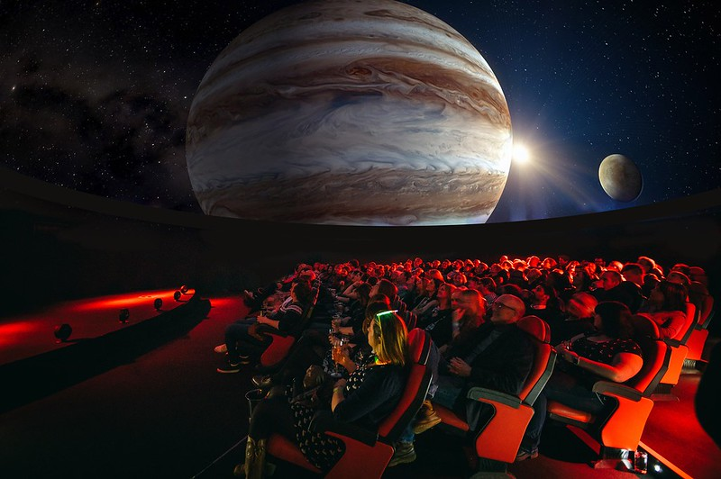 A full audience seated on red seats and a projection of the Earth and the sun in the planetarium at Dynamic Earth.