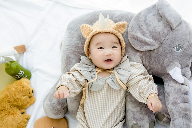 Charming asian baby happily lying over a stuffed elephant toy.