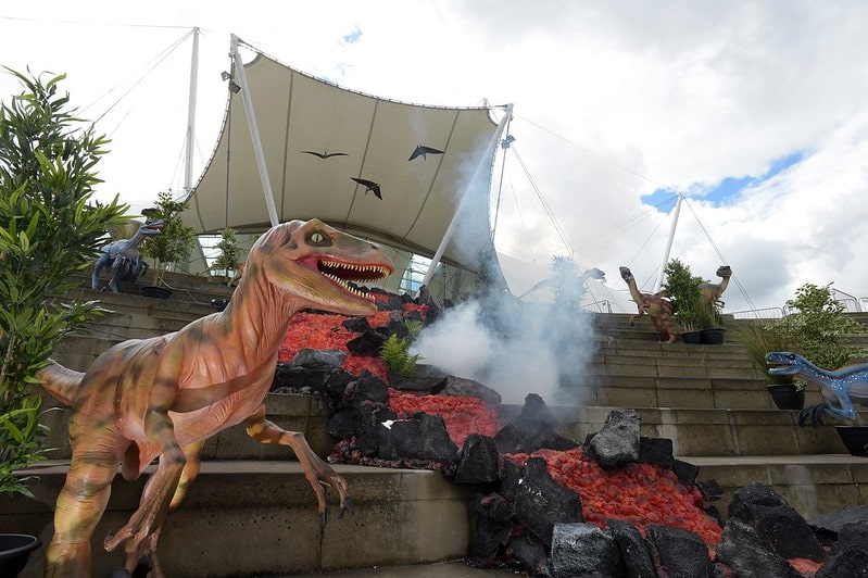 A dinosaur statue standing next to a river of lava at the Dynamic Earth museum.