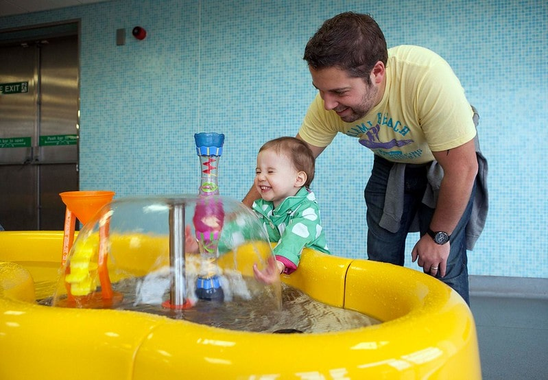 A toddler playing with a water machine with a parent at the science museum Techniquest.