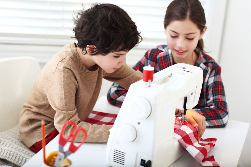 Two children using a sewing machine together