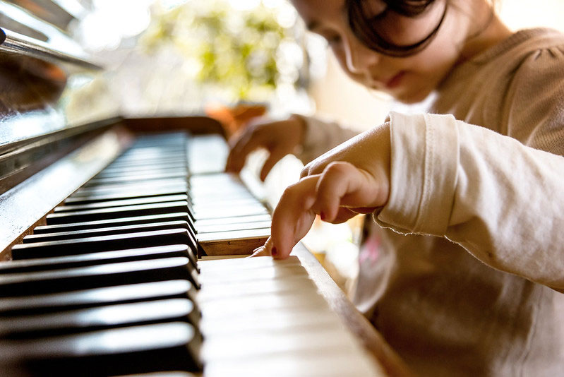 Cute little girl playing on old piano