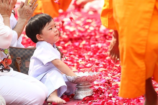 Thai baby happily attending the family's religious activity.