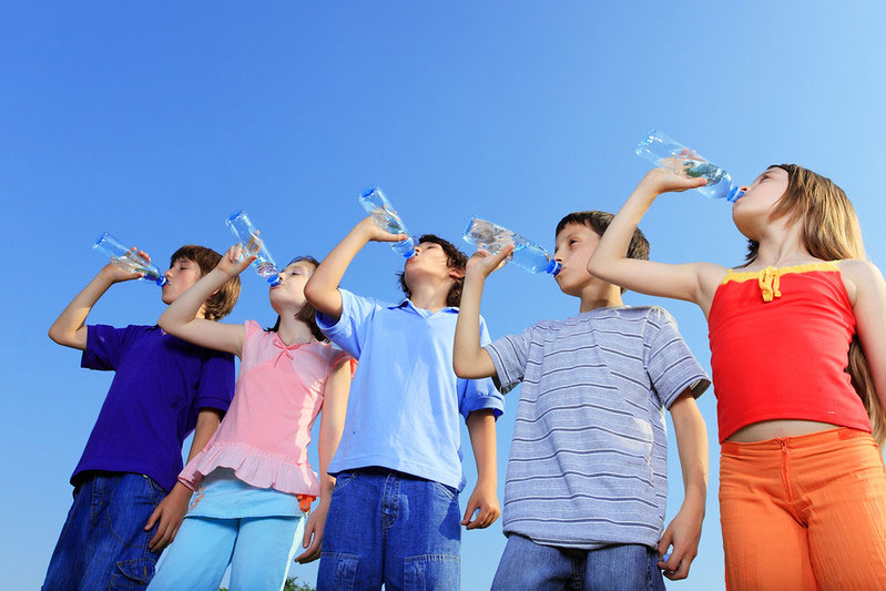Children drinking water from bottles against the blue sky