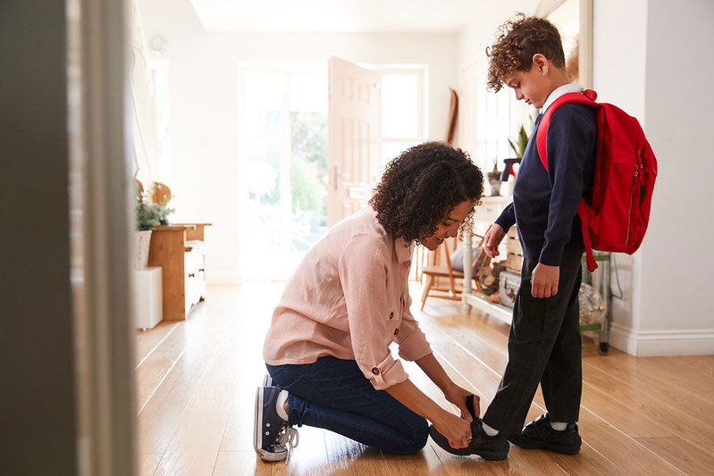 Mother at home tying her son's shoe before school