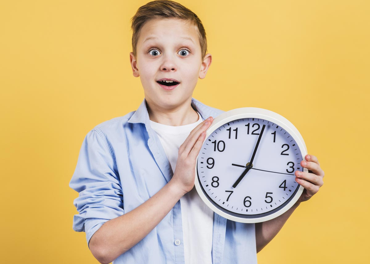 A boy holding a clock and looking surprised as his parents explain to him why the clocks go back.