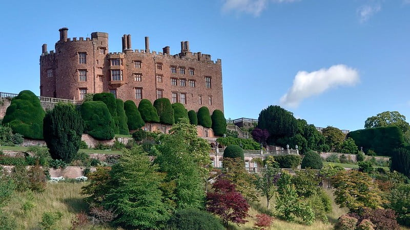 The exterior of Powis Castle sitting high on a rock with the formal gardens underneath.