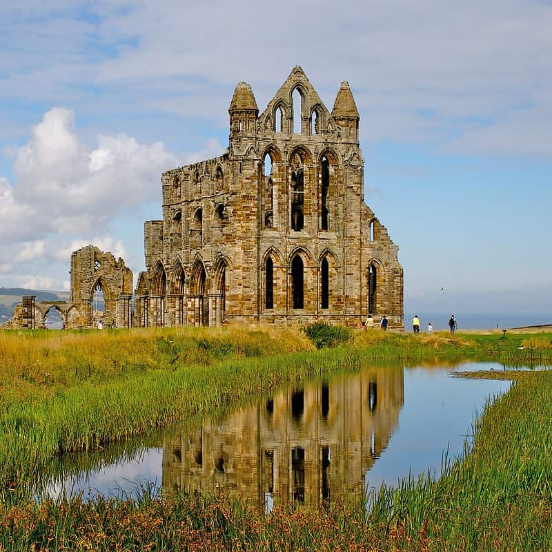 Whitby Abbey with water in the foreground on a clear day.