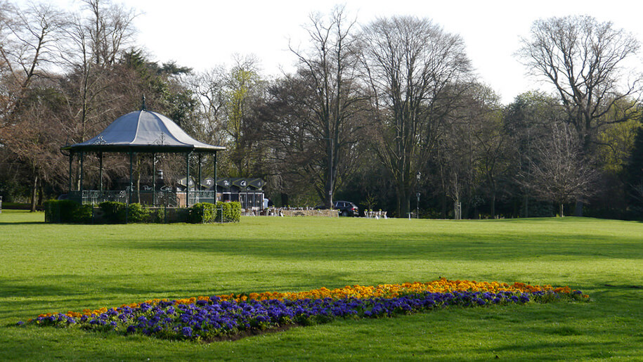 Bandstand in Abington Park with green grass and flowerbeds.
