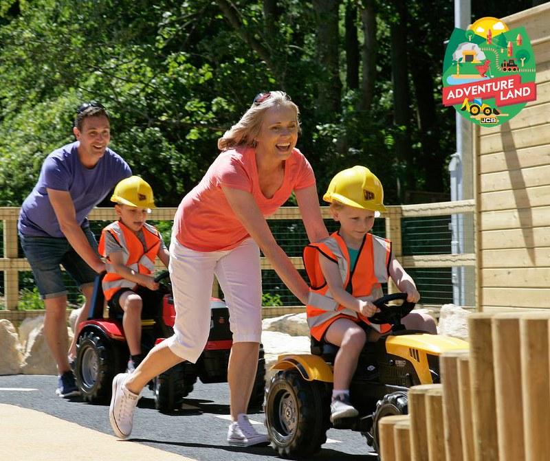Parents pushing their kids on Adventure Land diggers, having fun.