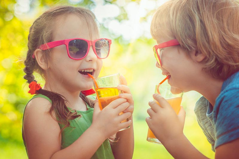 Little girl and boy drinking juice in park wearing sunglasses