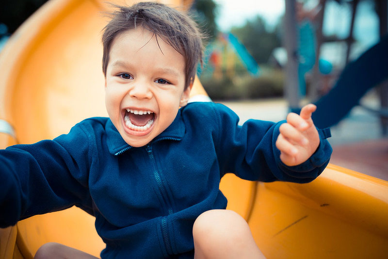 little boy sliding happily