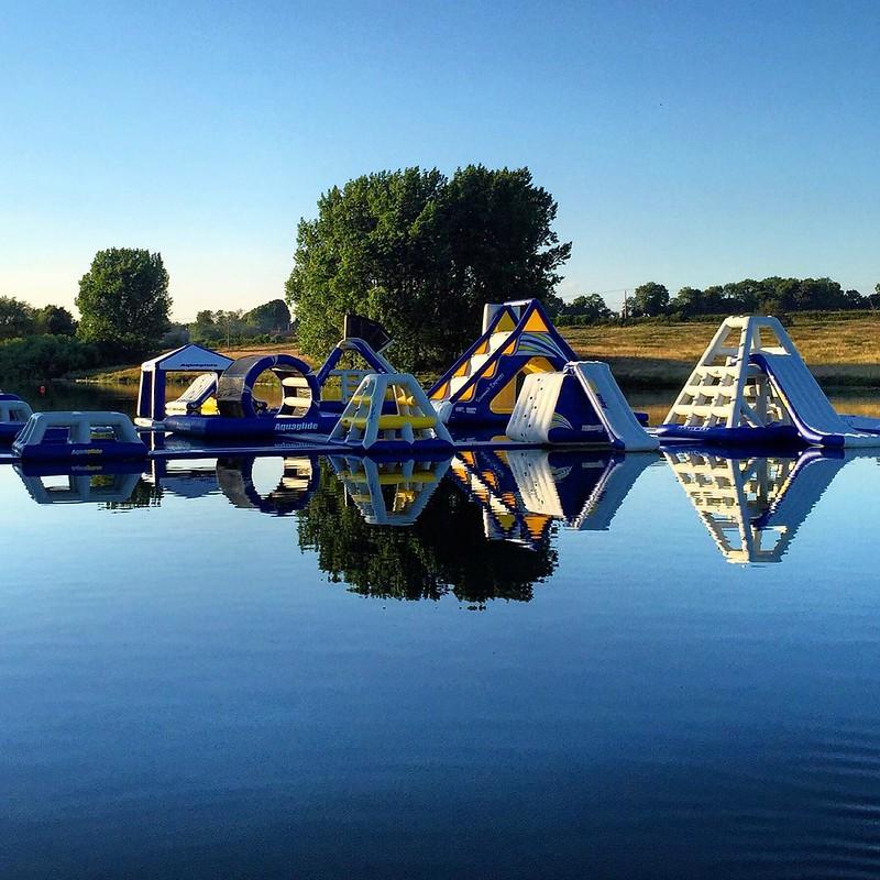 Inflatables reflected in Aqua Park Rutland lake.
