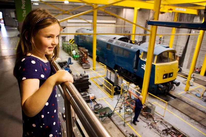 A girl looking over railings at the National Railway Museum.