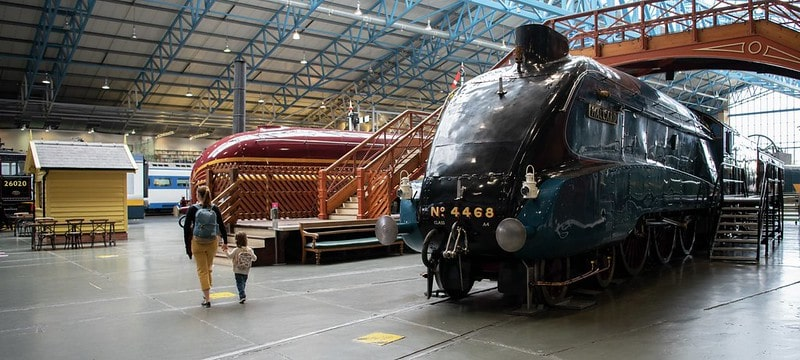 A mother and her child walking through the Great Hall train exhibit at the National Railway Museum.