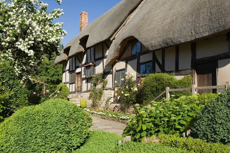 A close up picture of Anne Hathaway's Cottage next to a blossom tree.