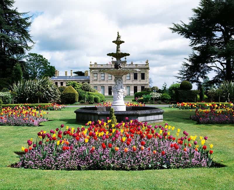 A fountain and colourful flowers in front of the house at Brodsworth Hall and Gardens.